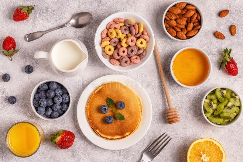 Breakfast with colorful cereal rings, pancakes, fruit, milk, juice. royalty free stock images