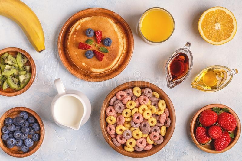 Breakfast with colorful cereal rings, pancakes, fruit, milk, juice. royalty free stock photo