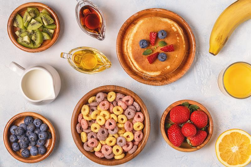 Breakfast with colorful cereal rings, pancakes, fruit, milk, juice. stock photography