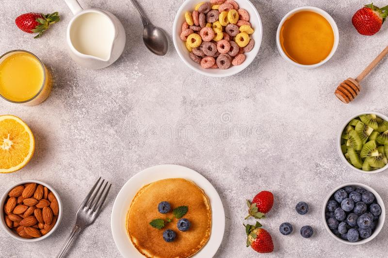 Breakfast with colorful cereal rings, pancakes, fruit, milk, juice. royalty free stock image