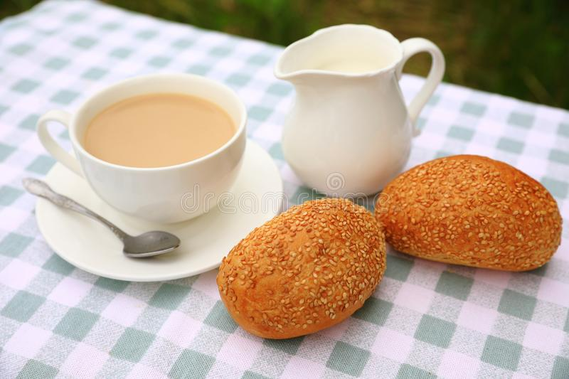 Breakfast composition of a cup of tea with cream, a creamer and sesame rolls royalty free stock image