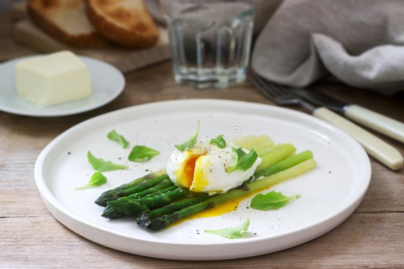Breakfast consisting of poached egg and boiled asparagus with butter and lettuce on a wooden surface. Rustic style stock photography