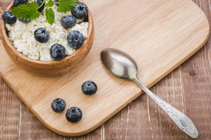 Breakfast with cottage cheese and blueberry on a wooden tray/breakfast with cottage cheese and blueberry on a wooden tray. Top. View, white, blueberries stock images