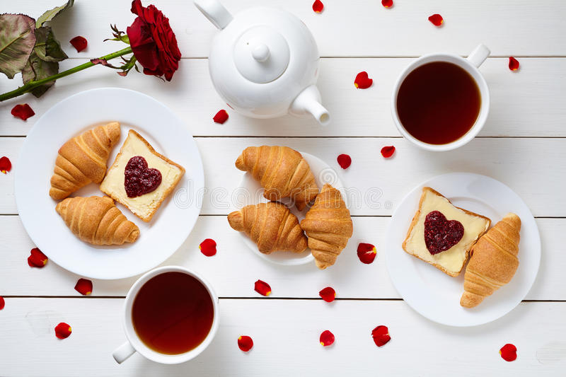 Breakfast for couple on Valentines Day with toasts, heart shaped jam, croissants, red rose flower, petals and tea stock photography