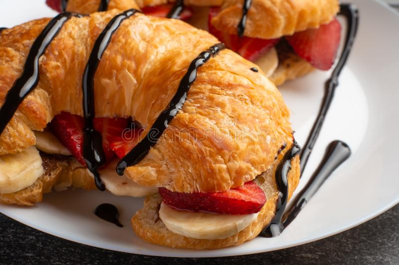 Breakfast with croissant, bananas and strawberries. chocolate closeup royalty free stock images