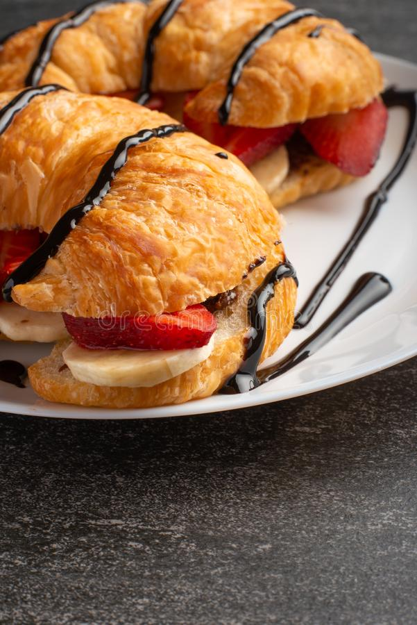 Breakfast with croissant, bananas and strawberries. chocolate closeup royalty free stock image
