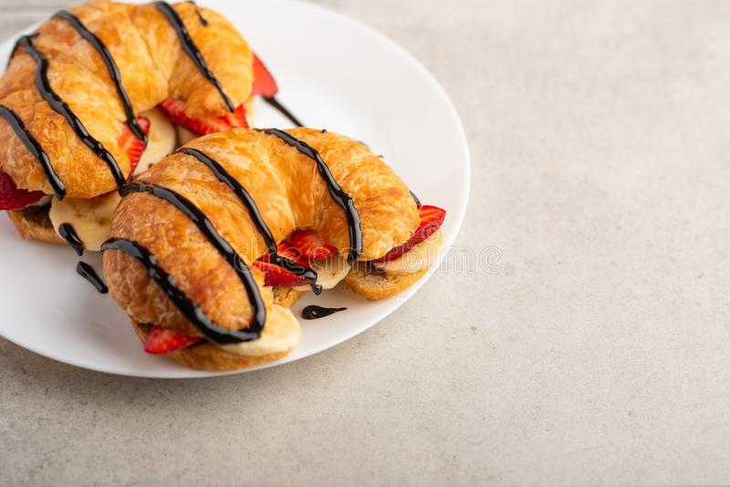 Breakfast with croissant, bananas and strawberries. with chocolate, with space stock image