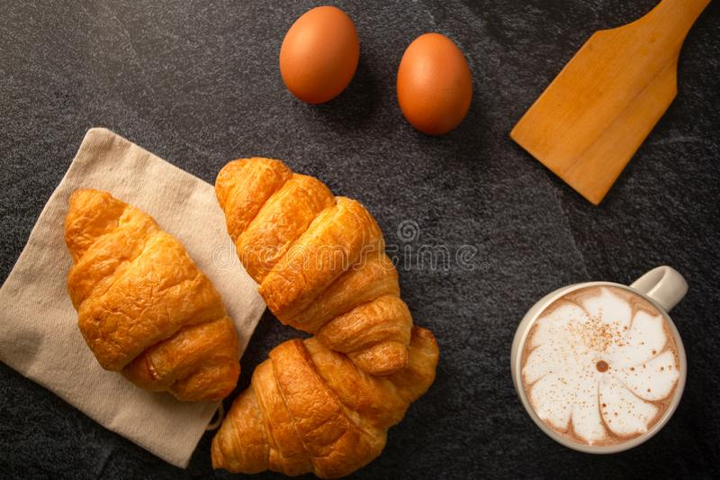 Breakfast with croissant with  cup of white coffee Put on a black background,,breakfast bread brown beverage morning,Concept: stock photo