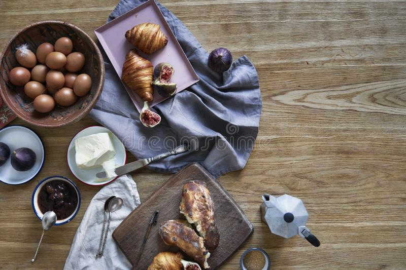 Breakfast with croissants, figs, coffee on wooden board over rustic wooden background, ceramics dishes, warm colors, above view stock image