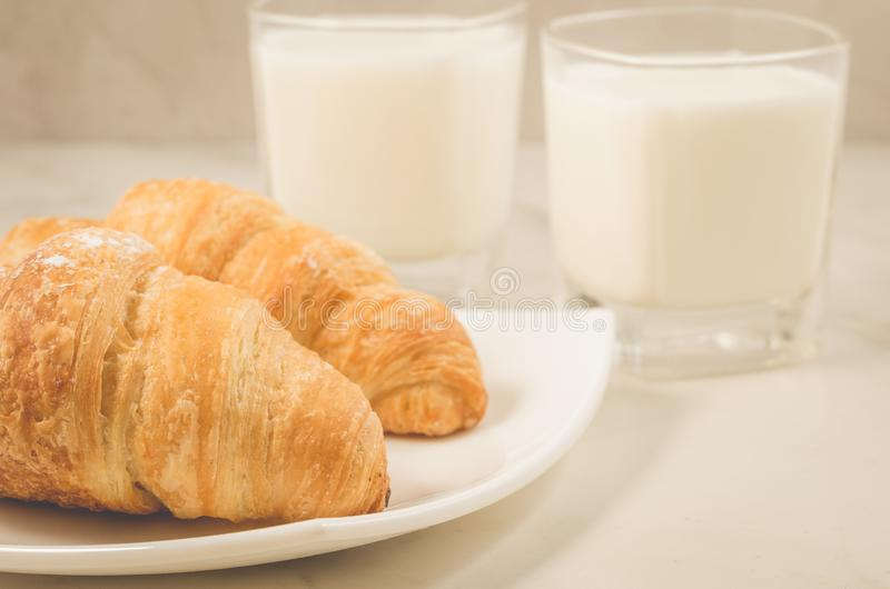 Breakfast with croissants and milk/croissants in a plate and glasses milk on a white table. Selective focus royalty free stock photography