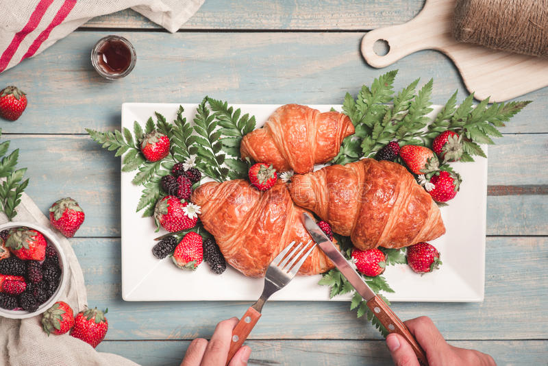 Breakfast with croissants and strawberry on blue wooden table. V. Iew from above stock images