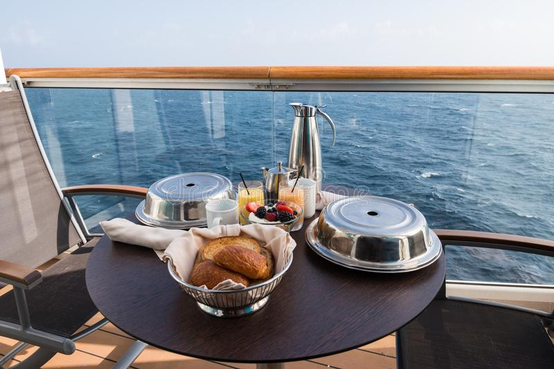 Breakfast on a cruise ship balcony. Table arrangement with breakfast on a cruise vacation. Fresh pastries, juices, smoothies, coffee and tea with silver covered royalty free stock images