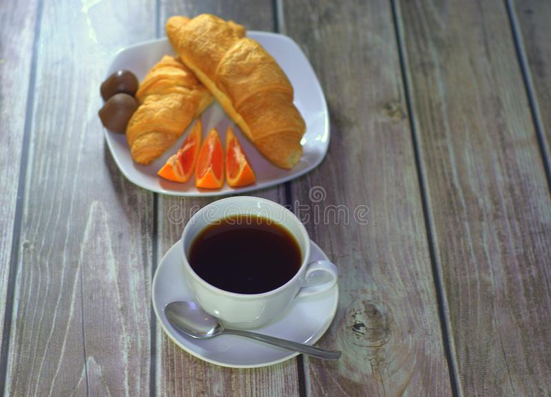 Breakfast, a cup of black coffee, croissants, chocolates and a piece of orange. Close-up royalty free stock images
