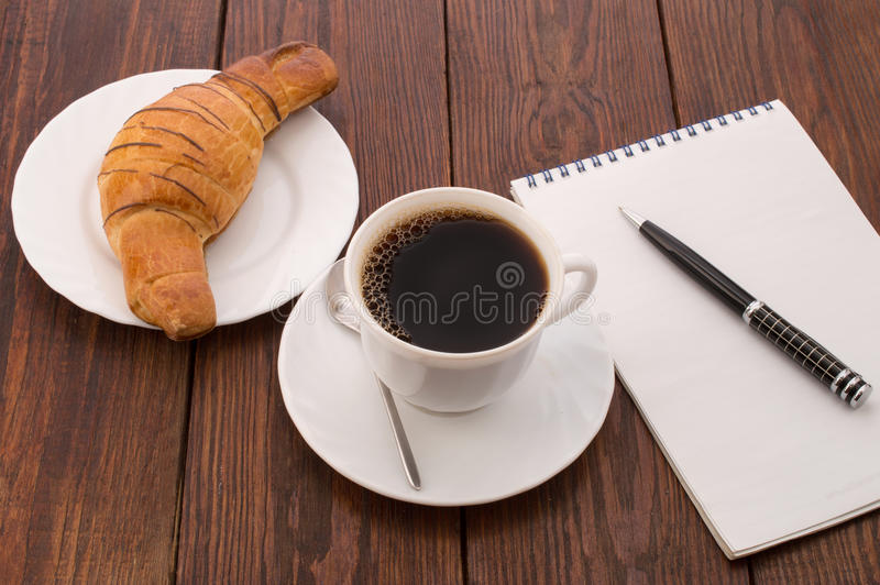 Breakfast with cup of black coffee, croissants and notebook. Breakfast with cup of black coffee, croissants, the tablet and notebook with pen isolated on white stock photography