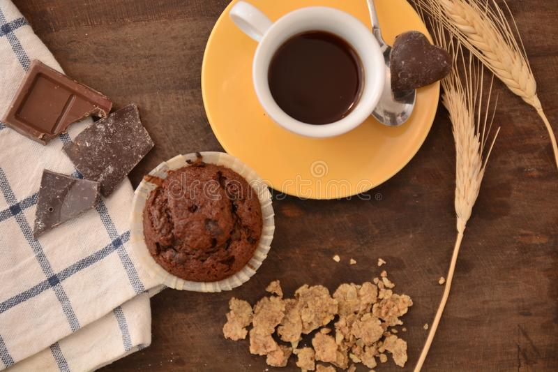 Breakfast cup coffe espresso black cereals muffin milk chocolate pieces on table morning food stock images