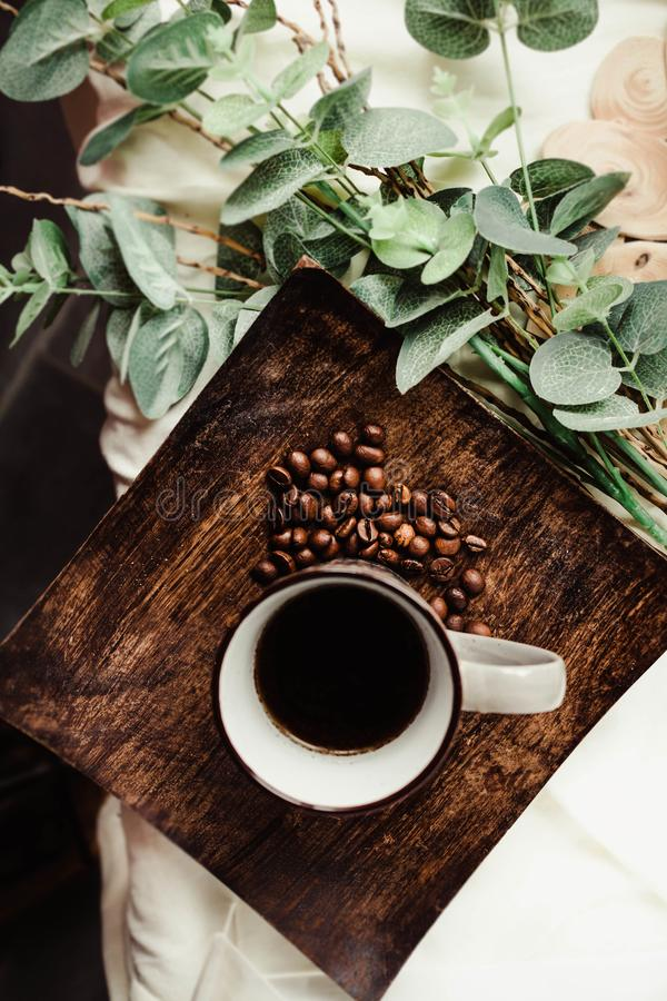 Breakfast. A cup of coffee, coffee beans in a wooden plate and g stock images