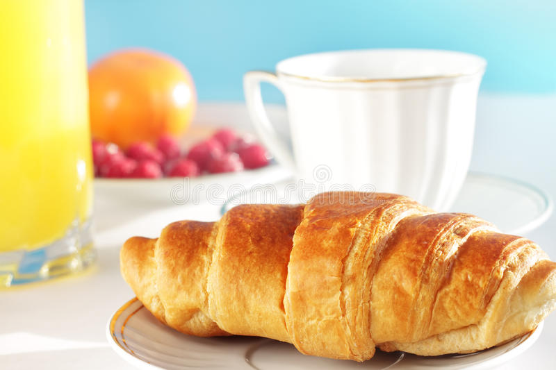 Breakfast. A cup of coffee and croissant royalty free stock images