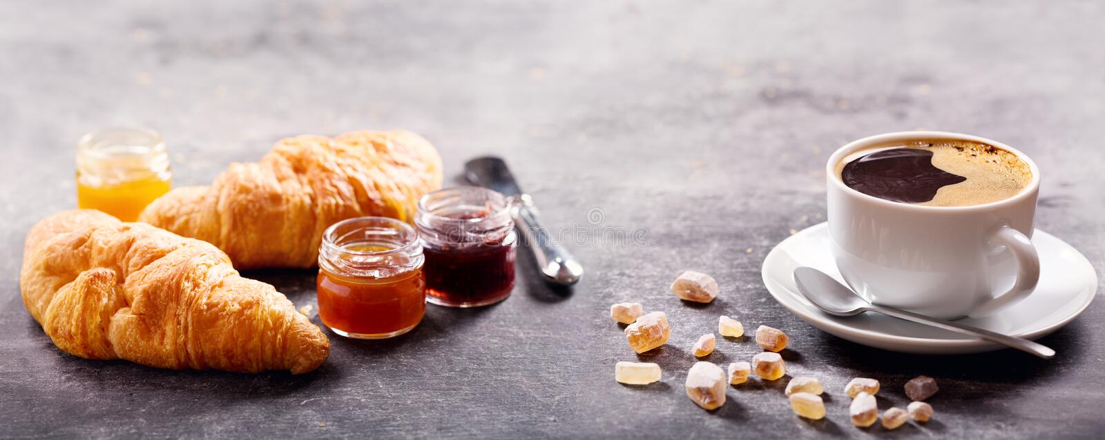 Breakfast with cup of coffee, croissant and fruit jam. On dark table royalty free stock images