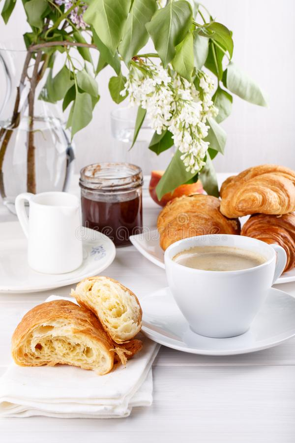 Breakfast - cup of coffee, croissants, jam and fruits on white table royalty free stock photos
