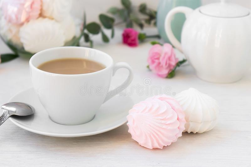 Breakfast with a cup of coffee and two homemade white and pink marshmallow zephyr on a gentle morning. Selective focus royalty free stock photo