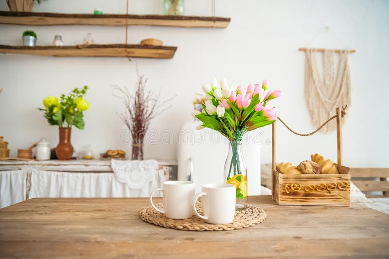 Breakfast cups and fruit. Spring tulips on the table. Wooden table in a bright rustic-style kitchen. Scandinavian style in the int. Erior of the kitchen royalty free stock photo