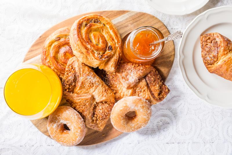 Breakfast with different French Pastries, Juice and Jam. Breakfast with different French Pastries, such as Almond Croissants, Donuts, Pain Au Raisins, also with royalty free stock photos