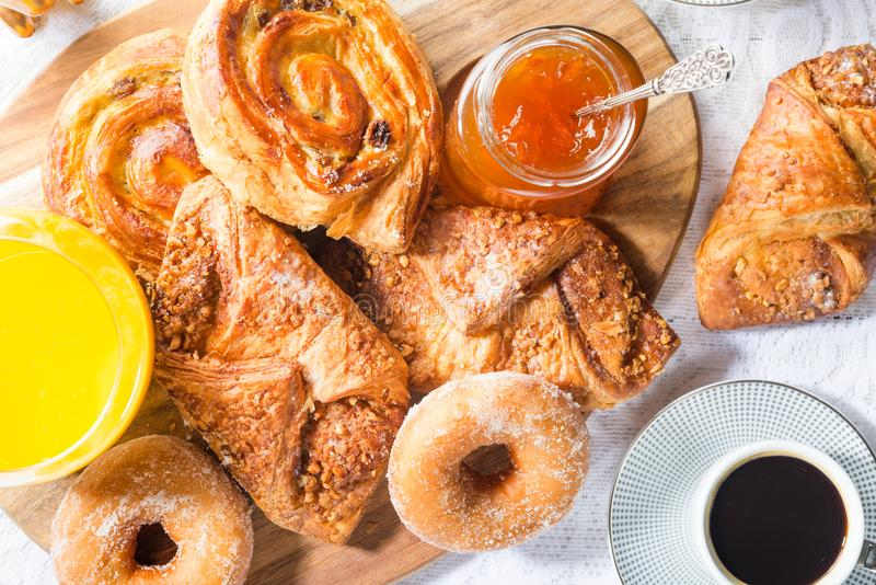 Breakfast with different French Pastries, Juice and Jam. Breakfast with different French Pastries, such as Almond Croissants, Donuts, Pain Au Raisins, also with stock photography