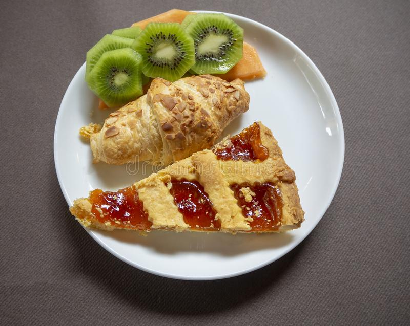 Breakfast: dish with home made jam tart, croissant, melon and kiwi fruit stock image