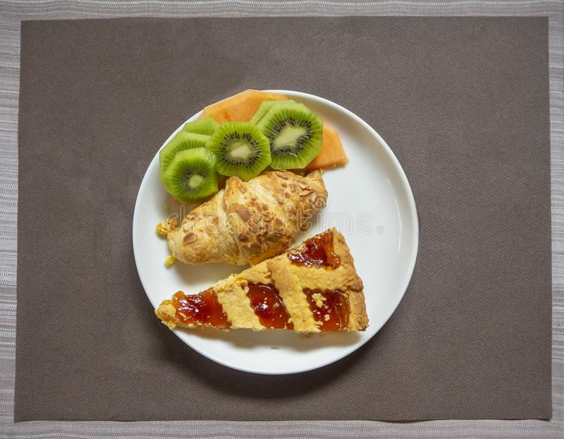 Breakfast: dish with home made jam tart, croissant, melon and kiwi fruit royalty free stock images