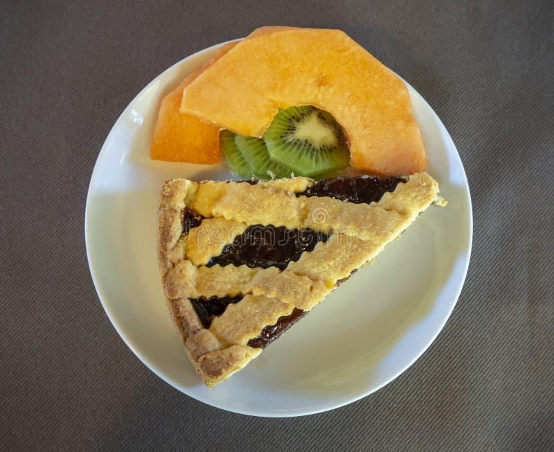 Dish with home made jam tart, melon and kiwi fruit stock photos