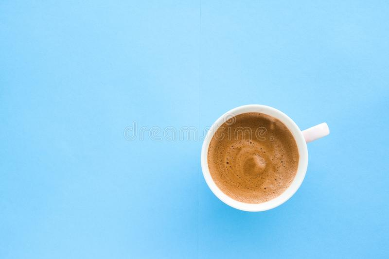 Hot aromatic coffee on blue background, flatlay. Breakfast, drinks and modern lifestyle concept - Hot aromatic coffee on blue background, flatlay royalty free stock image