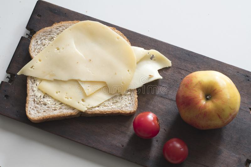 Breakfast with Dutch cheese,  brown bread, apple and  cherry tomatoes on wooden cutting board stock photo