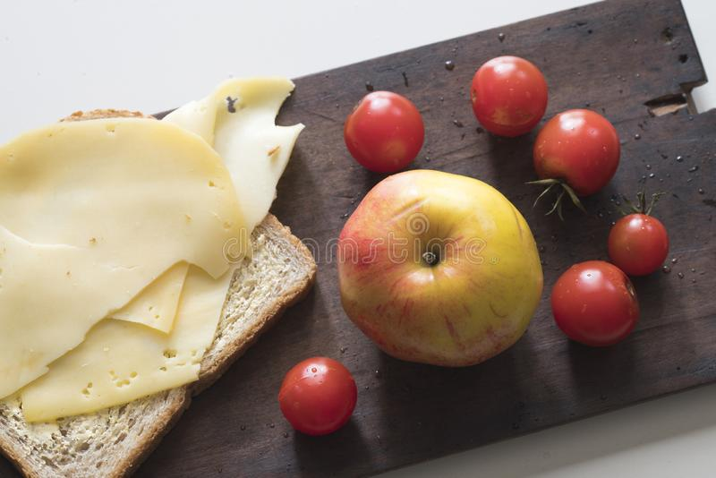 breakfast with Dutch cheese, brown bread, apple and cherry tomatoes on wooden cutting board stock image