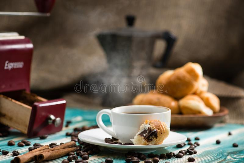 Breakfast with espresso cup of hot coffee and croissant on a woo. Den table royalty free stock images