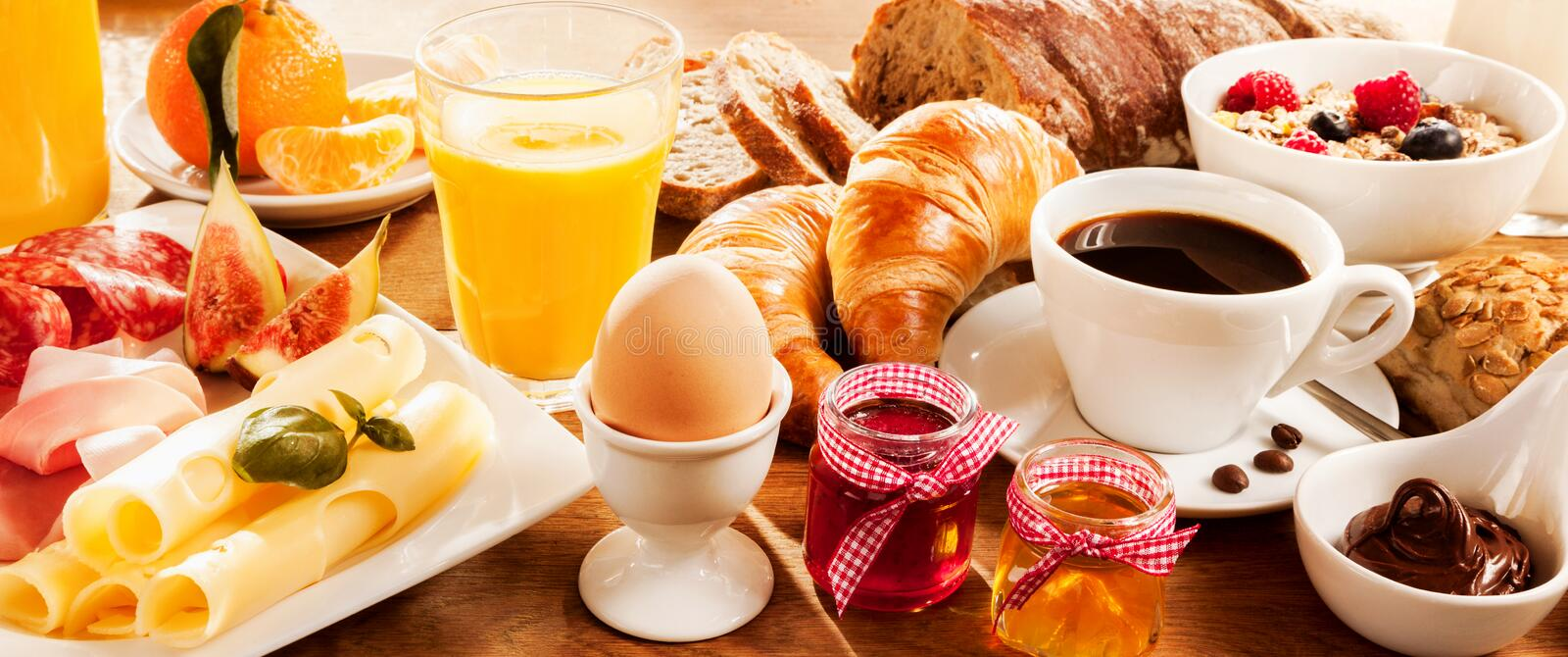 Breakfast feast on table. Breakfast feast with egg, meat, bread, coffee and juice royalty free stock image