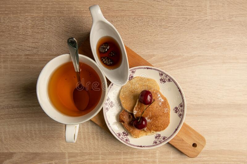 Breakfast flat lay: cup of tea, pancakes and jam stock photography