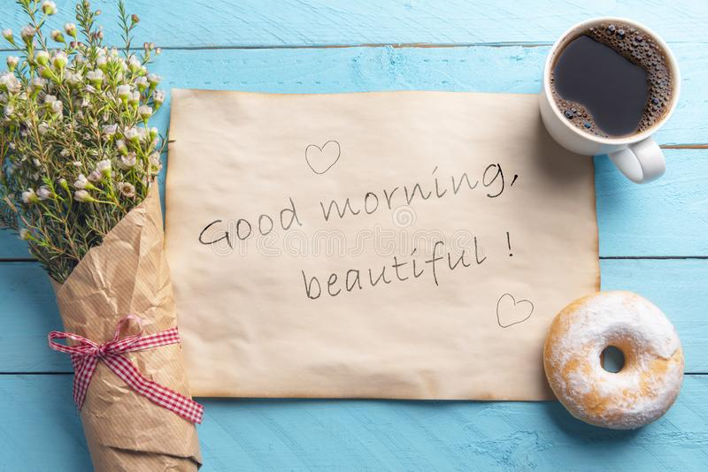 Breakfast with flowers and coffee and message. Good morning beautiful text. Above view. Vintage paper with the good morning beautiful message and hearts, a royalty free stock image