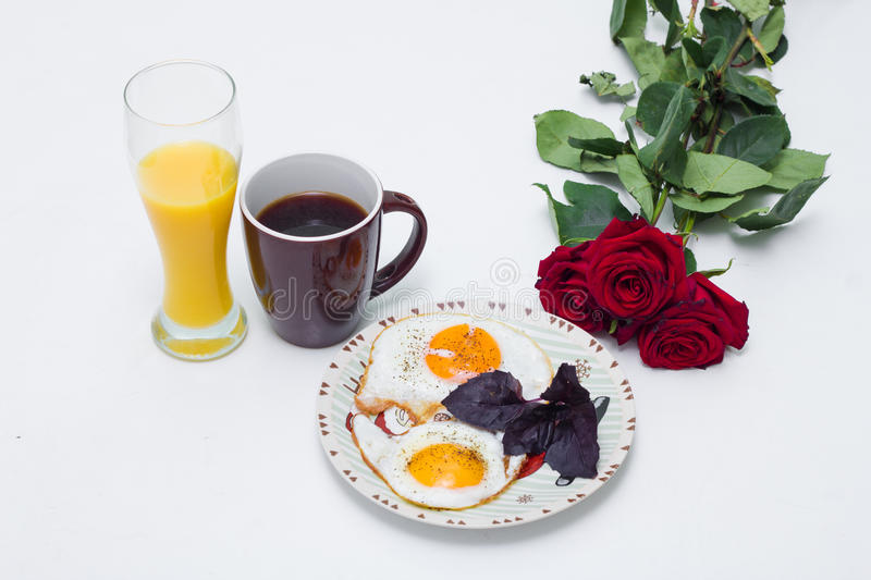 Breakfast with flowers, orange juice, coffee and eggs stock images