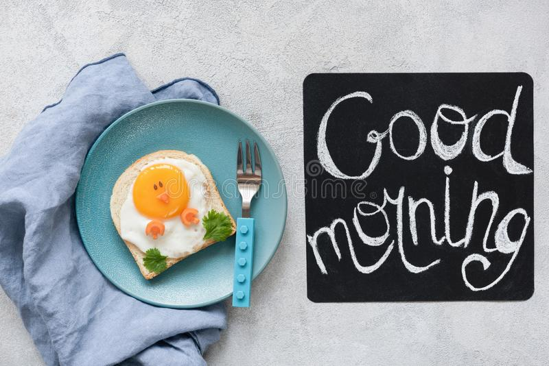 Breakfast food kids. Funny toast with egg and good morning text. On a chalkboard. Top view stock photo
