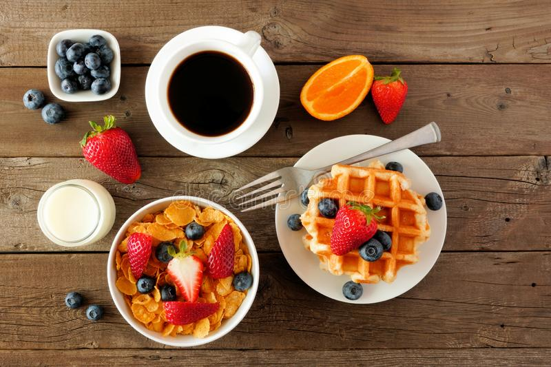 Breakfast food table scene. Fruits, cereal, waffles, milk and coffee. Top view over wood. royalty free stock photos