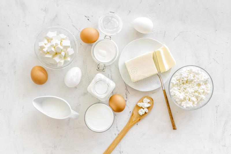 Dairy products from farm with milk, eggs, cottage, butter, yougurt on white marble background top view stock photography