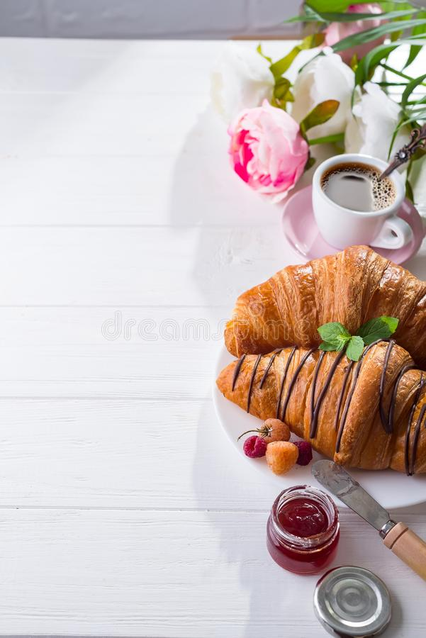 Breakfast freshly baked croissant decorated with jam and chocolate, flowers on wooden table in a kitchen with copy space royalty free stock image