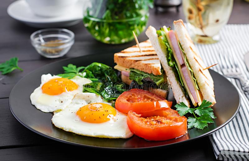 Breakfast: fried egg, spinach, tomatoes and club sandwich stock photo