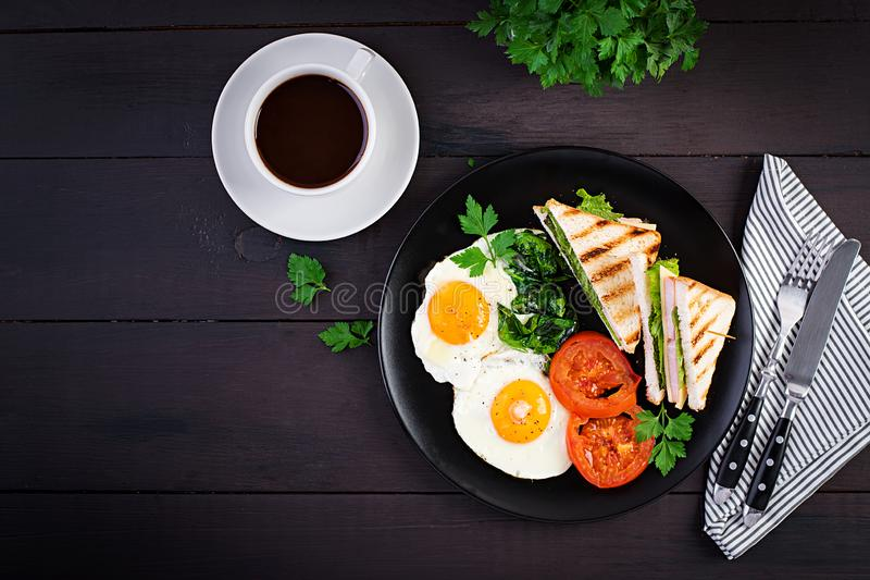 Breakfast: fried egg, spinach, tomatoes and club sandwich royalty free stock photography