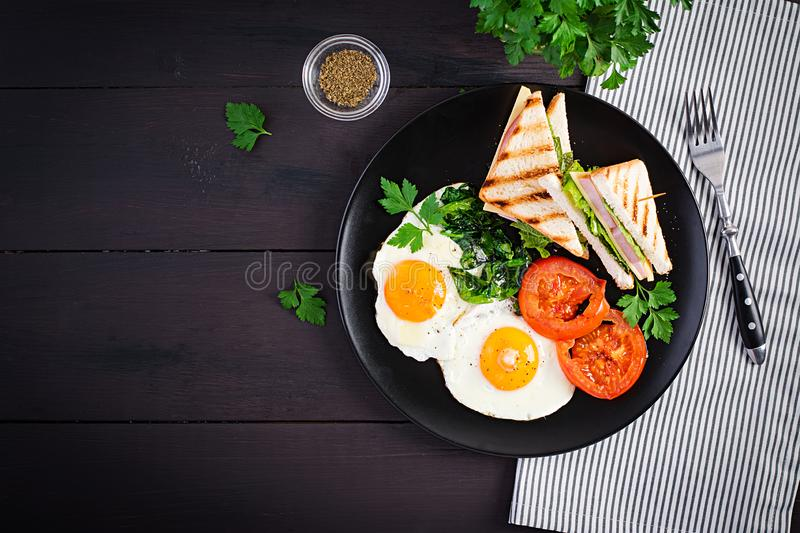 Breakfast: fried egg, spinach, tomatoes and club sandwich royalty free stock images