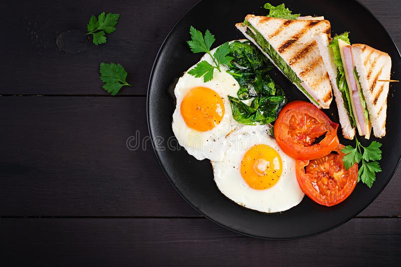 Breakfast: fried egg, spinach, tomatoes and club sandwich stock photography