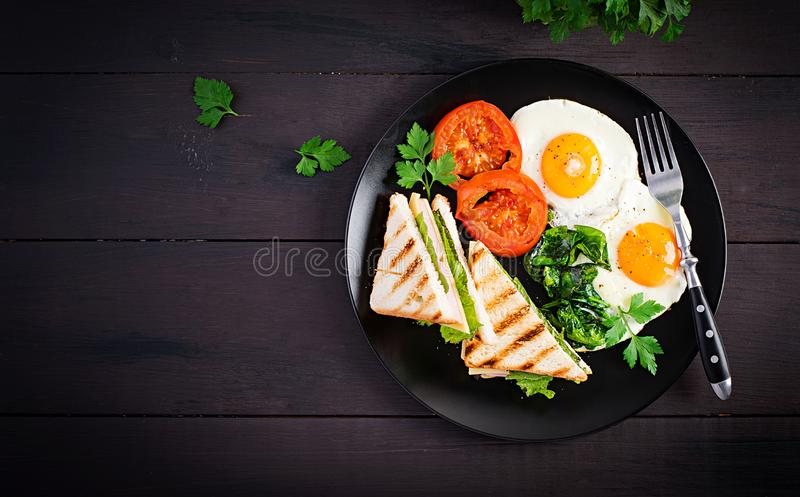 Breakfast: fried egg, spinach, tomatoes and club sandwich royalty free stock photo