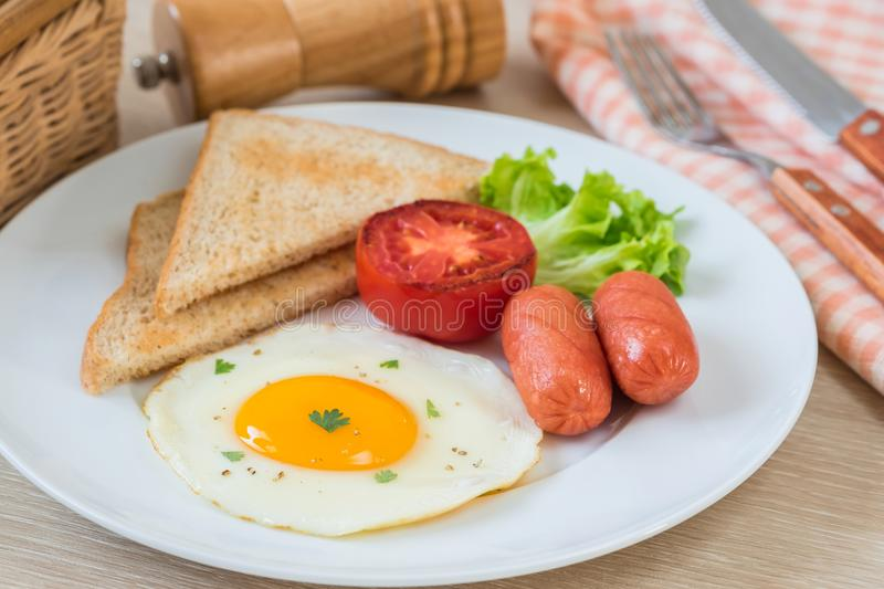 Breakfast with fried egg, toast, sausage and vegetable on plate. Breakfast with fried egg, toast, sausage and vegetable on white plate royalty free stock images