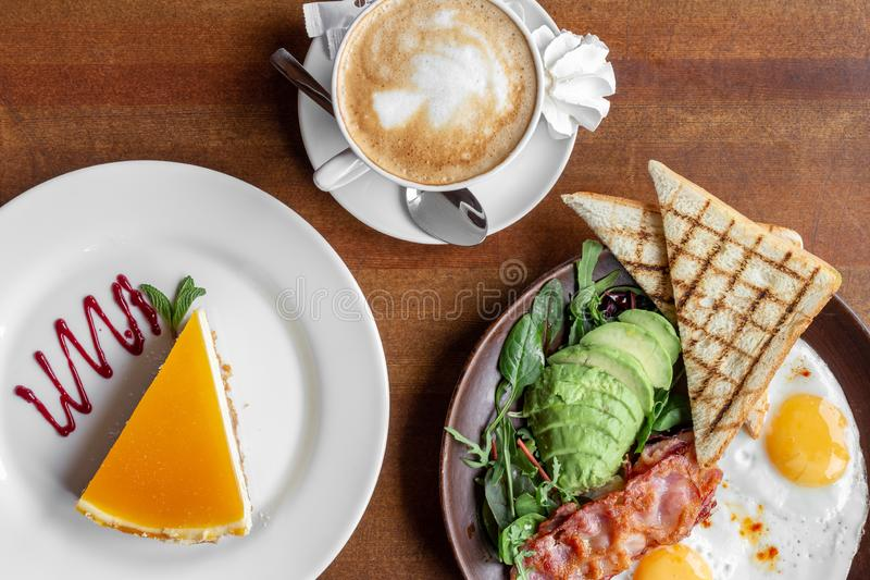 Breakfast of fried eggs with fried bacon, avocado and toast with coffee and cheesecake royalty free stock images