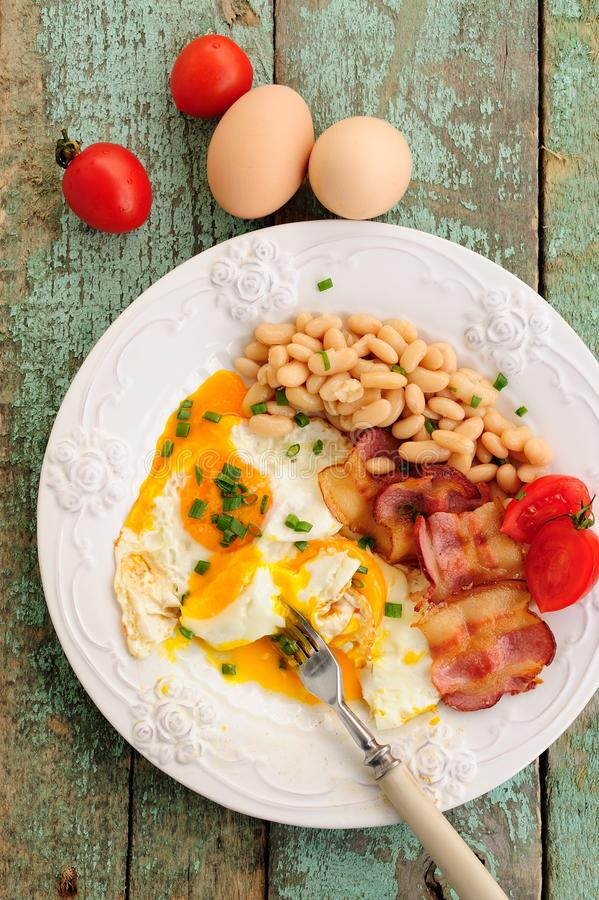 Breakfast of fried eggs, bacon, beans and tomatoes on wooden tab stock images